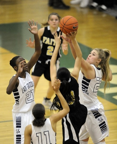 Spring Valley guard Jessica Rafay, right, blocks a shot attempt by Faith Lutheran point guard Madison Bocobo while Alana Walker (21) defends in the first quarter of the Division I-A Southern Regio ...