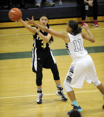 Faith Lutheran point guard Madison Bocobo passes in front of Spring Valley guard Kayla Harris (11) in the first quarter of the Division I-A Southern Region girls basketball championship game at Sp ...