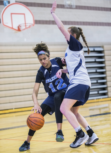 Foothill junior Rae Burrell (12) drives baseline past Rhianna Cox (21) at Mannion Middle School on Monday, Feb. 20, 2017, in Henderson. Burrell is poised to lead the Falcons into the Class 4A stat ...