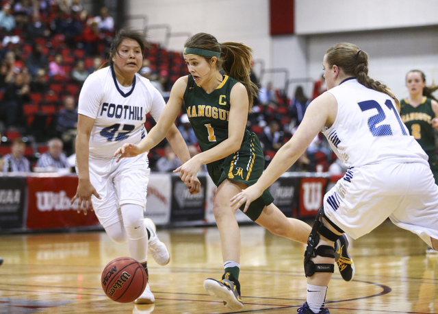 Bishop Manogue guard Katie Turner (1) drives to the basket between Foothill's Trinity Betoney (42) and Rhianna Cox (21) during the Class 4A girls state basketball semifinals at the Cox Pavilion in ...