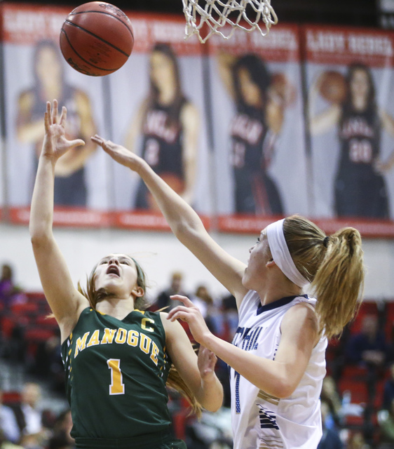 Bishop Manogue guard Katie Turner (1) shoots to score over Foothill's Kylie Vint (11) during the Class 4A girls state basketball semifinals at the Cox Pavilion in Las Vegas on Thursday, Feb. 23, 2 ...