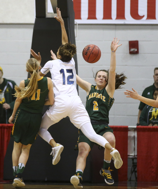 Foothill's Rae Burrell (12) collides with Bishop Manogue forward Maddie Camacho (2) during the Class 4A girls state basketball semifinals at the Cox Pavilion in Las Vegas on Thursday, Feb. 23, 201 ...