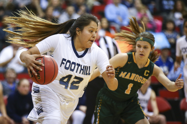 Foothill's Trinity Betoney (42) drives the ball against Bishop Manogue guard Katie Turner (1) during the Class 4A girls state basketball semifinals at the Cox Pavilion in Las Vegas on Thursday, Fe ...