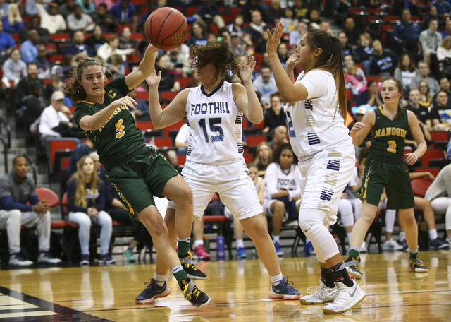 Bishop Manogue guard Malia Holt (5) passes the ball as Foothill's Bri Rosales (15) and Trinity Betoney (42) defend during the Class 4A girls state basketball semifinals at the Cox Pavilion in Las  ...