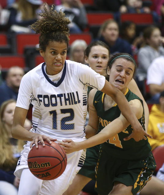 Foothill's Rae Burrell (12) drives against Bishop Manogue forward Hannah Reviglio (14) during the Class 4A girls state basketball semifinals at the Cox Pavilion in Las Vegas on Thursday, Feb. 23,  ...