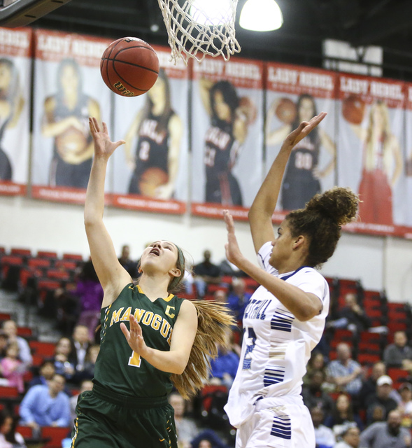 Bishop Manogue guard Katie Turner (1) goes to the basket over Foothill's Rae Burrell (12) during the Class 4A girls state basketball semifinals at the Cox Pavilion in Las Vegas on Thursday, Feb. 2 ...