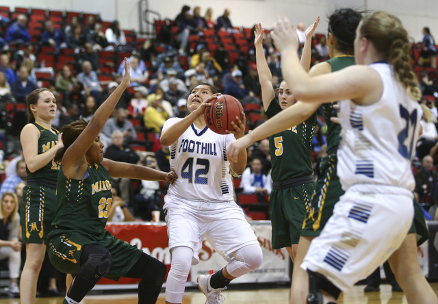 Foothill's Trinity Betoney (42) drives to the basket between Bishop Manogue defends during the Class 4A girls state basketball semifinals at the Cox Pavilion in Las Vegas on Thursday, Feb. 23, 201 ...