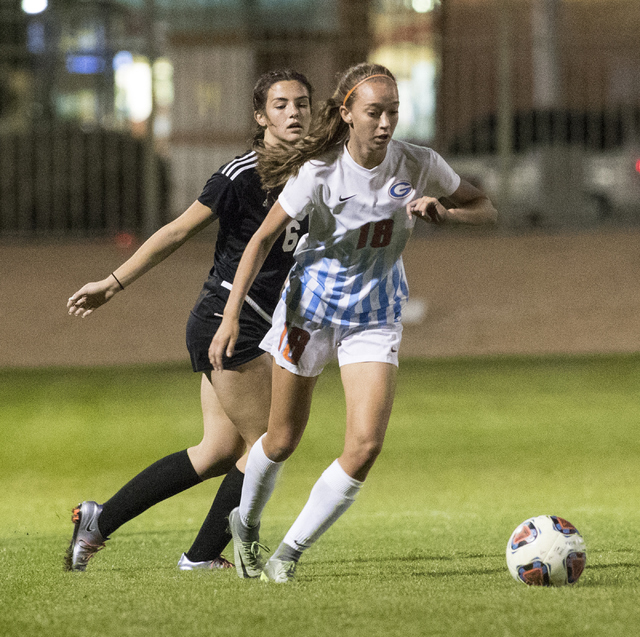 Taylor Cox (18) from Bishop Gorman High School, battles for the ball against Holly Lindholm (6) Holly Lindholm, during the Sunset Region girls soccer semifinal game at Bettye Wilson Soccer Complex ...