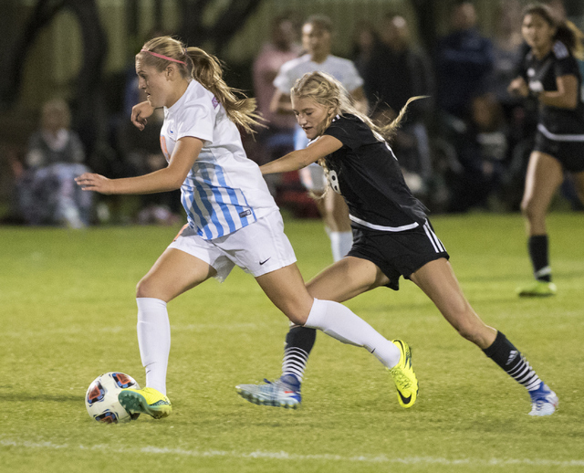 Arlie Jones (19) from Bishop Gorman High School battles for the ball against Alexis Lloyd (8) from Palo Verde School during the Sunset Region girls soccer semifinal game at Bettye Wilson Soccer Co ...