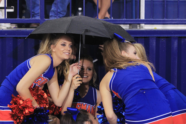 Bishop Gorman cheerleaders huddle under an umbrella during a rain delay before their game against St. John Bosco Friday, Sept. 26, 2014 at Bishop Gorman. (Sam Morris/Las Vegas Review-Journal)