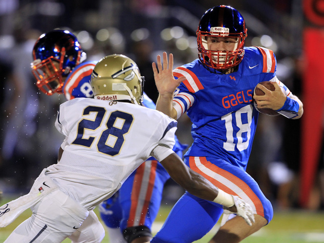 Bishop Gorman quarterback Tate Martell scrambles away from St. John Bosco defensive back Traveon Beck during their game Friday, Sept. 26, 2014 at Bishop Gorman. Gorman won the game 34-31. (Sam Mor ...