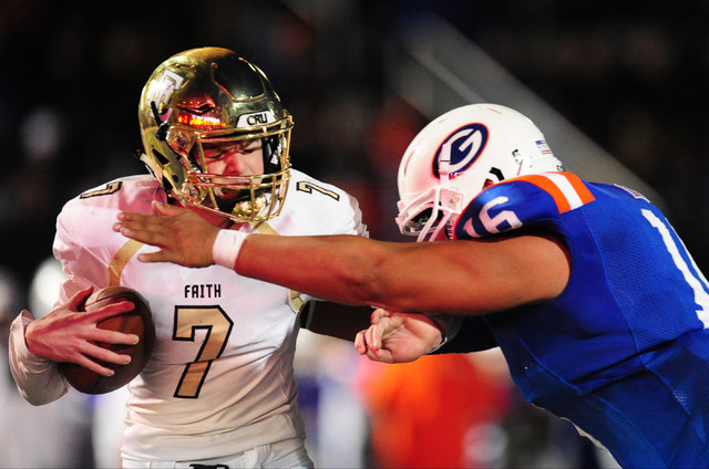 Bishop Gorman defensive end Haskell Garrett , right, sacks Faith Lutheran quarterback Sagan Gronauer in the endzone for a safety in the first half of their prep football game at Bishop Gorman High ...