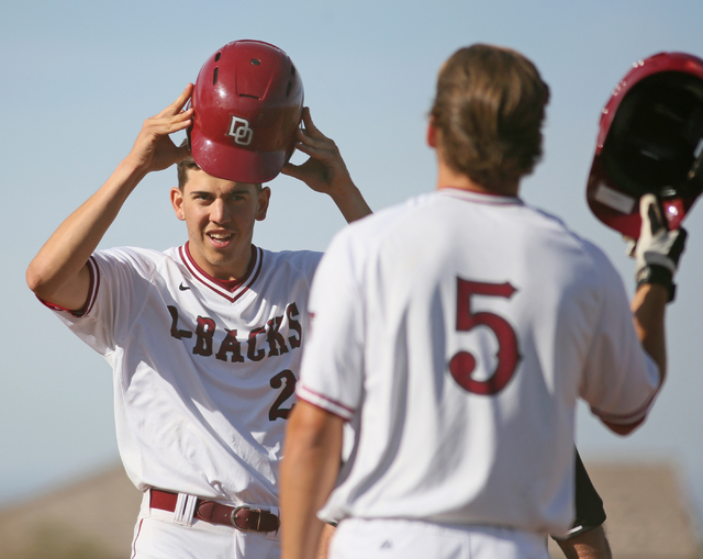 Desert Oasis senior Nolan Kingham, left, takes off his batting helmet after hitting a homerun in the fourth inning of a game against Cimarron-Memorial at Desert Oasis High School Monday, March 23, ...