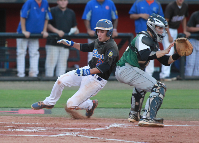 Bishop Gorman's Grant Robbins (27) slides into home past Rancho catcher Zach Barnhart (21) during the American Legion state baseball championship game on Saturday. The Rams rallied for a 9-8 victo ...