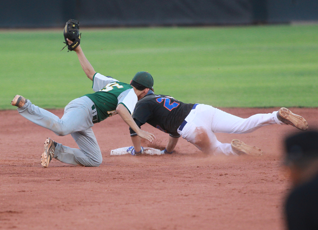 Bishop Gorman's Grant Robbins (27) dives safely into second base past Rancho's Braulio Santiaguin (15) during the American Legion state baseball tournament on Saturday. Rancho rallied for a 9-8 wi ...