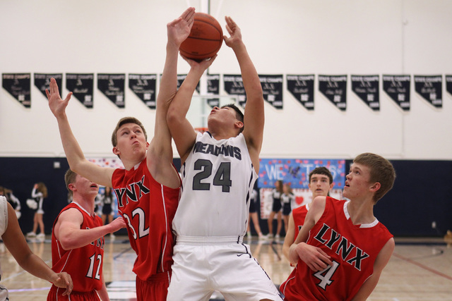 Lincoln County's Derek Shumway blocks a shot by The Meadows forward Michael Jin during their game Saturday at The Meadows. Shumway had 17 points as Lincoln County won 81-72  in overtime. (Sam Morr ...