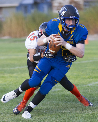 Pahranagat Valley Panthers quarterback Tabor Maxwell (2) runs the ball against Wells, Nevada players during the season opening eight-man high school football game in Alamo, Nevada on Friday, Aug.  ...