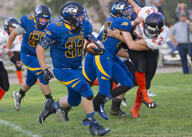 Pahranagat Valley Panthers running back Christian (32) Higbee runs the ball against Wells, Nevada players during the season opening eight-man high school football game in Alamo, Nevada on Friday,  ...