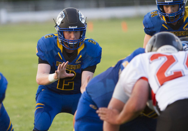 Pahranagat Valley Panthers quarterback Tabor Maxwell hikes the ball against Wells, Nevada players during the season opening eight-man high school football game in Alamo, Nevada on Friday, Aug. 26, ...