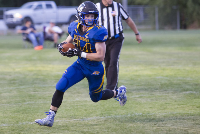 Pahranagat Valley Panthers tight end Ike Taylor runs the ball against Wells, Nevada players during the season opening eight-man high school football game in Alamo, Nevada on Friday, Aug. 26, 2016. ...