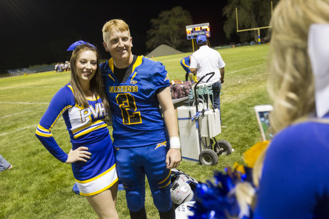 Pahranagat Valley Panthers quarterback Tabor Maxwell, second left, poses with a Panthers cheerleader after defeating Wells, Nevada following the season opening eight-man high school football game  ...
