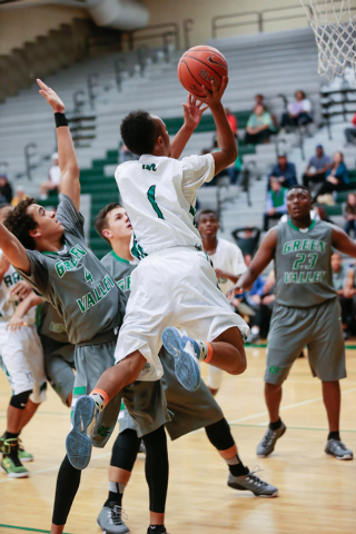 Rancho High School's David McKeever (1) leaps up and around Green Valley High defender Xavier Jarvis (4) earlier this season. McKeever averages 15.8 points and hopes to lead the Rams to their firs ...
