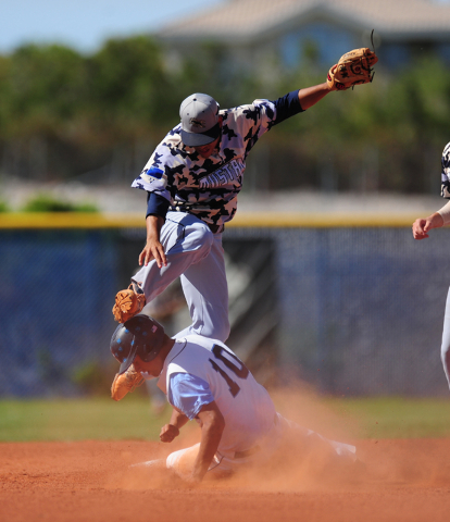 Shadow Ridge shortstop Eric Jordan jumps over Centennial base runner Frank Sessa while turning a double play in the third inning of their prep baseball game at Centennial High School in Las Vegas  ...