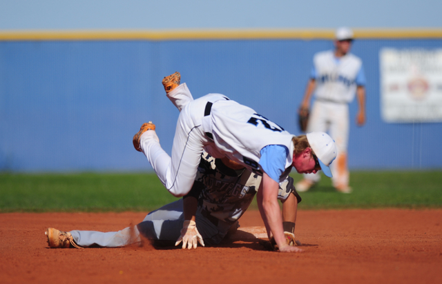 Centennial second baseman Jake Rogers falls over Shadow Ridge baserunner Trevin Reynolds after Reynolds hit a double in the fifth inning of their prep baseball game at Centennial High School in La ...