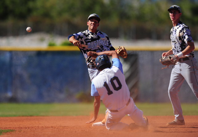 Shadow Ridge shortstop Eric Jordan turns a double play as Centennial base runner Frank Sessa slides into second base in the third inning of their prep baseball game at Centennial High School in La ...
