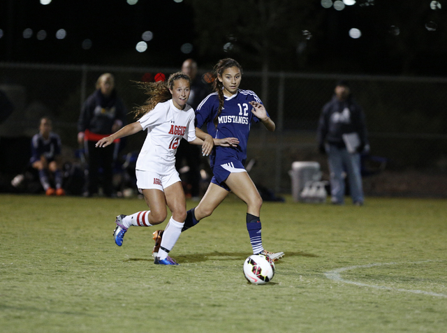 Arbor View's Hayley Vicente (12) and Shadow Ridge's Casey Childers (12) close in on the ball during the Sunset Region semifinals on Thursday. Vicente scored the winning goal with less than nine mi ...