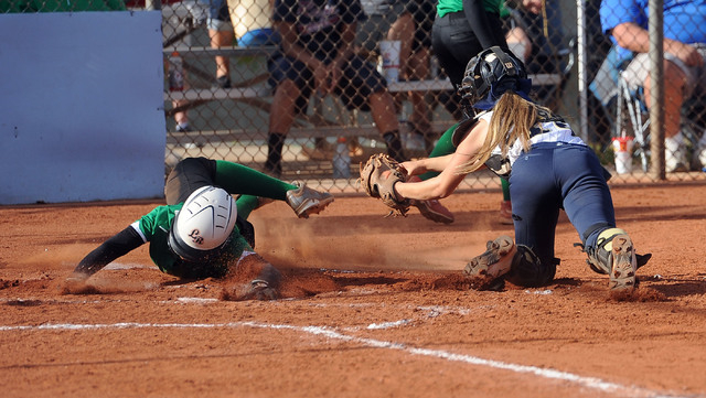 Rancho's Jahnae Davis-Houston, left, slides around the tag of Foothill catcher Hannah Stevens during the second inning of the Sunrise Region softball tournament winners' bracket final Thursday. Ho ...