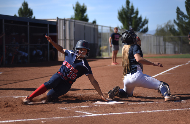 Coronado's Taylor Okamura (10) scores at home plate against Foothill's Haleigh Olive (1) during their softball game at Coronado High School in Henderson on Wednesday, May 11, 2016. Coronado defeat ...