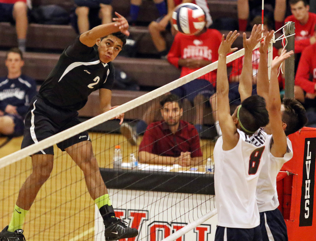 Rancho's Martin Rodriguez, from left, spikes the ball as Liberty's Daniel Lusung and Brycen Ivester go up for a block during the boys volleyball Sunrise Region tournament quarterfinals at Las Vega ...