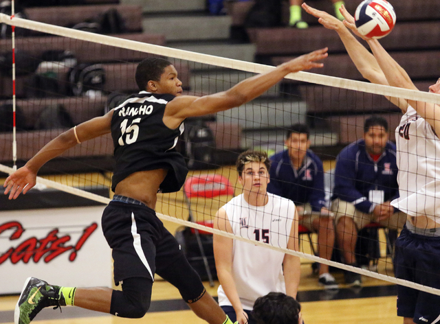 Rancho's Lamont Taylor, from left, spikes the ball as Liberty's Ryan Taggart stands ready and Mike Meatovich blocks during the boys volleyball Sunrise Region tournament quarterfinals at Las Vegas  ...