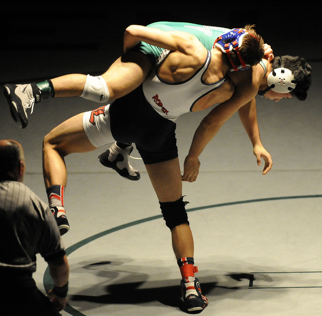 Liberty's Storm Roper of Liberty, center, slams Green Valley's Giullian Nakamatsu to the mat during the 152-pound final of Sunrise Region Wrestling tournament at Green Valley High School in Hender ...