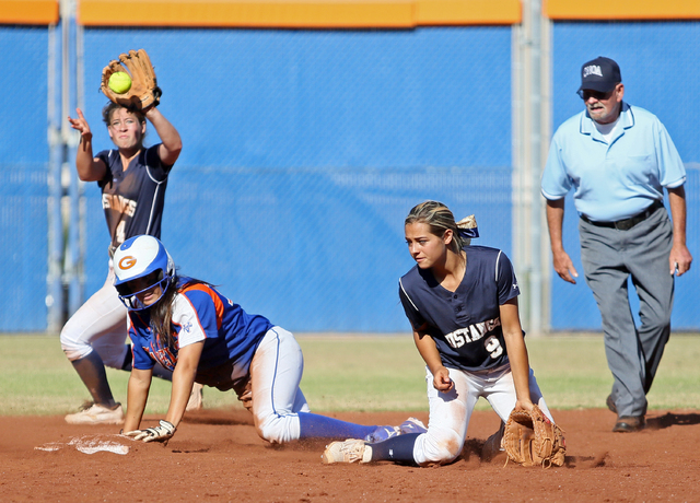 Bishop Gorman's Shelby Estocado, left, slides into second base past Shadow Ridge's Sofia Meza, back left (4), and Joryan Brewer, front center (9), during a first round of the Sunset Region tournam ...