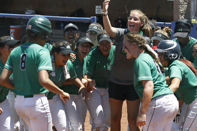 Rancho players gather at home base to congratulate teammate Kayla Coles on her home run against Liberty at Bishop Gorman High School in Las Vegas on May 14, 2016. Rancho won the game 8-0, making t ...