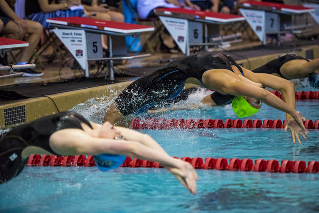 Abby Richter, green cap, of Green Valley comes off the block at the start of the girls 100 yard backstroke final of the Sunrise Region swim meet at the Bucky Buchanan Natatorium on the campus of U ...
