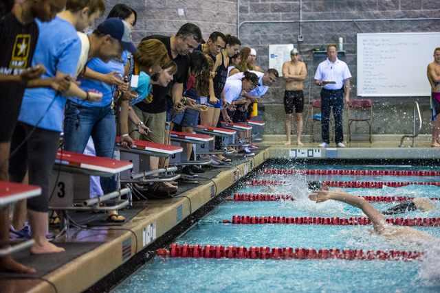 Time keepers lean in to see which swimmer touches the wall first during the Sunrise Region high school swim meet at the Bucky Buchanan Natatorium on the campus of UNLV in Las Vegas on Saturday, Ma ...