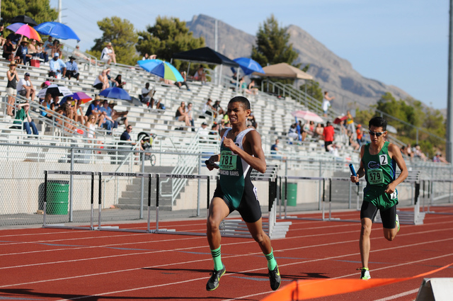 Rancho's Lorenzo Johnson, left, finishes first followed by Green Valley's Lenny Rubi during the boys 3,200-meter relay at the Sunrise Region meet on Saturday. (Erik Verduzco/Las Vegas Review-Journal)