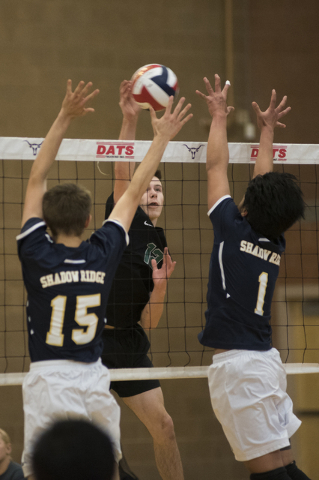 Palo Verde's Chandler Juilfs (12) goes up to spike the ball against Shadow Ridge's Jacob Ludwig (15) and NJ Makiawi (1) during their Sunset Regional volleyball semifinal match held at Legacy High  ...