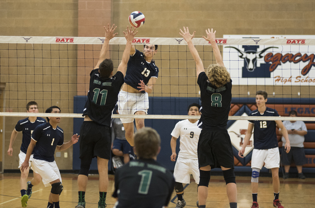 Shadow Ridge's Cody Heathcock (13) spikes the ball against Palo Verde's Michael Simister (11) and Grant Tingey (8) during their Sunset Regional volleyball semifinal match held at Legacy High Schoo ...