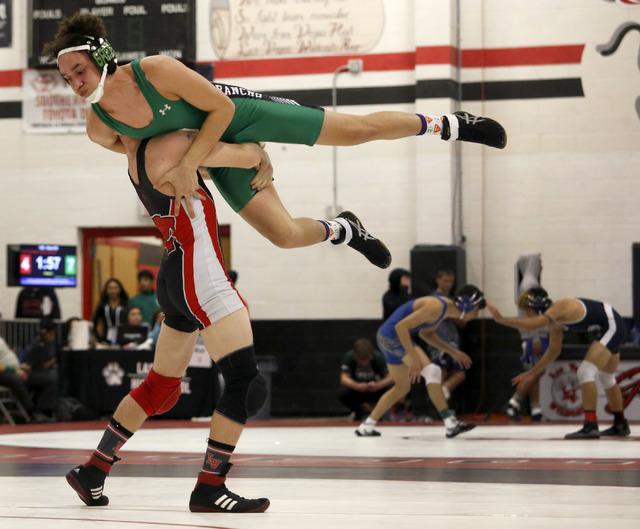Las Vegas's Daniel Law, bottom, lifts Rancho's Joel Serrano during a 132 pounder match at the Sunrise Region wrestling meet on Friday, Feb. 3, 2017, in Las Vegas. (Christian K. Lee/Las Vegas Revie ...