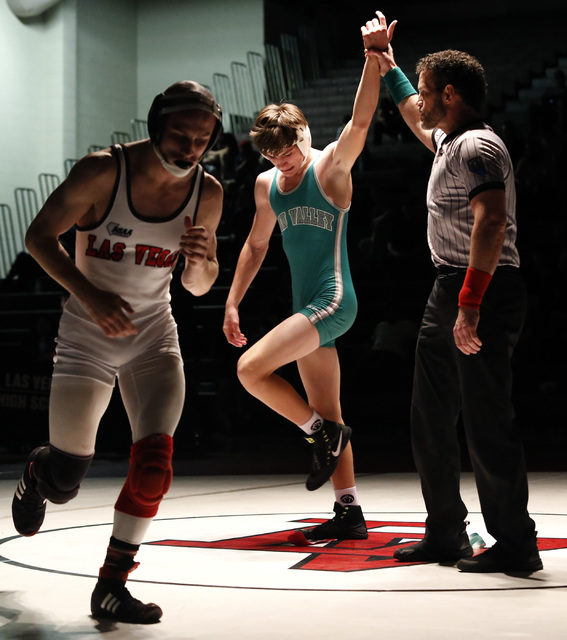 Green Valley's Justus Scott, green singlet, hand is raised as Las Vegas's Daniel Law runs off the mat after a 132 pounder match at the Sunrise Region wrestling meet on Saturday, Feb. 4, 2017, in L ...