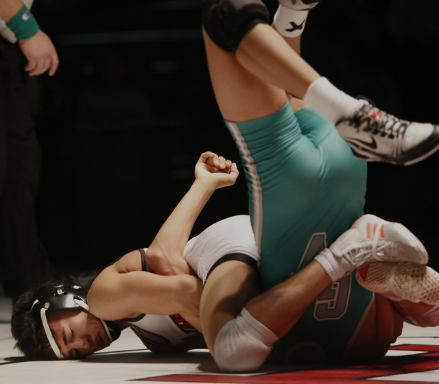 Las Vegas's Antonio Saldate, white singlet, attempts to pin Green Valley's David Kalayanaprapruit during a 120 pounder match at the Sunrise Region wrestling meet on Saturday, Feb. 4, 2017, in Las  ...