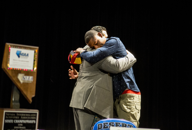 Senior Randal Grimes hugs Desert Pines coach Tico Rodriguez after signing to play college football for University of Southern California at Desert Pines High School, Las Vegas, February. 1, 2017.  ...