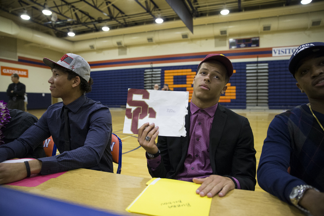 Bishop Gorman's Bubba Bolden, center, who committed to attending University of Southern California during Signing Day at Bishop Gorman High School on Wednesday, Feb. 1, 2017, in Las Vegas. (Erik V ...