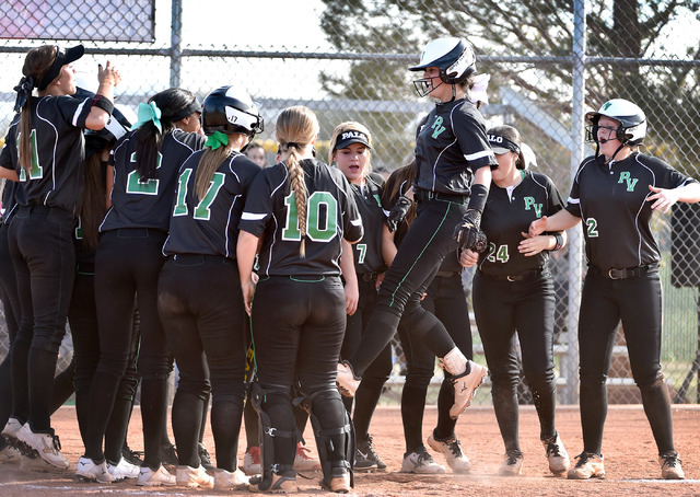 Palo Verde's Cara Beatty, 3rd right, jumps on home plate with her teammates celebrating after she hit a home run against Centennial during a high school softball game at Palo Verde High School on  ...
