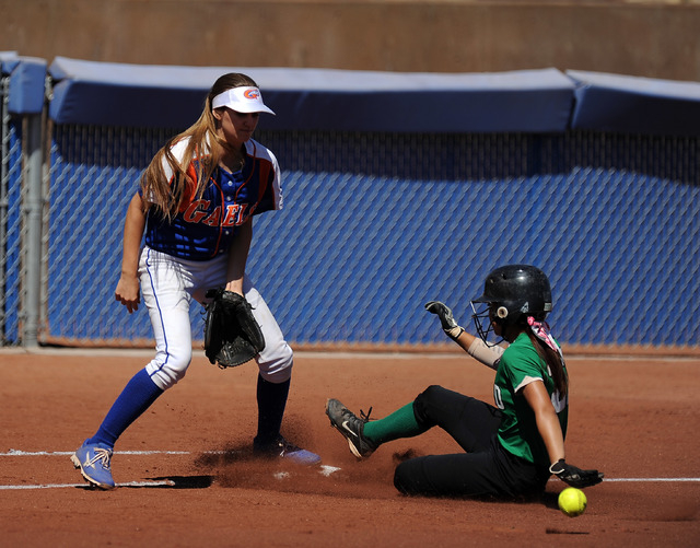 Rancho base runner Katerina Anthony safely advances to third base on a Rancho base hit as Bishop Gorman third baseman Morgan Blanner fields the throw in the first inning of their prep softball gam ...