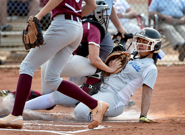 Sierra Vista's Kalei Watkins is tagged out as she slides home against Faith Lutheran catcher Sara Zelazny during a high school softball game at Faith Lutheran High School on Monday, April 20, 2015 ...